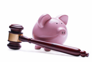 Porcelain pink piggy bank next to a wooden judge gavel, concept of savings, economic litigations and auctions, close-up with shadow on white